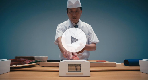 This is a scene about a sushi chef putting sushi on a scale. Play movie.